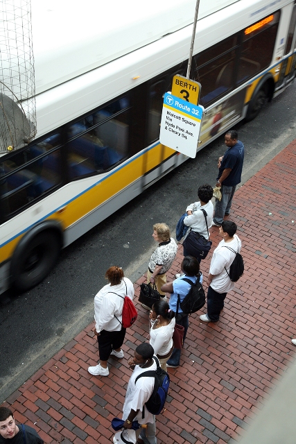 Bus passengers wait to board.