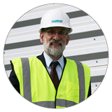 Photograph of article author William S. Kuttner, an older white man with a beard and glasses, wearing a yellow reflective vest and hardhat.