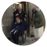 Three men exit an elevator, one using a wheelchair and one with a cane.